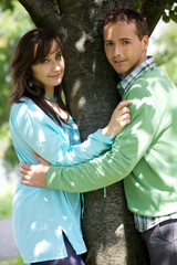 Young couple with arm around by tree