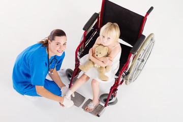 overhead of happy nurse bandaging little girls foot