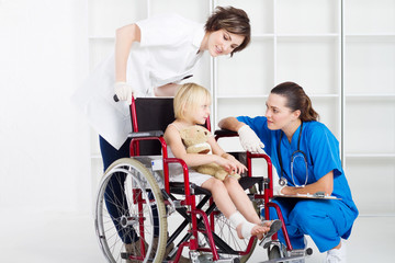caring nurse and doctor chatting to girl in wheelchair