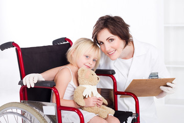 portrait of kind nurse and little patient in wheelchair