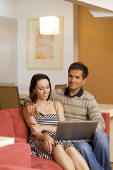 Couple using bank card online with a laptop