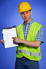 architect in coveralls and hardhat pointing at clipboard