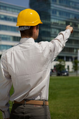 Architect in hardhat pointing at construction site
