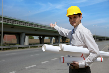 Portrait of architect in hardhat holding blueprint and gesturing