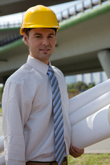 architect holding blueprint at construction site