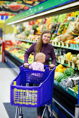 Mother with baby shopping in supermarket