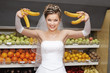 Smiling bride holding bananas in supermarket