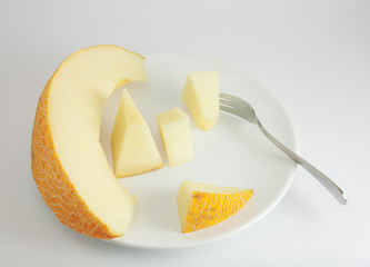 Melon slices on a plate with fork. A photo on a grey background.