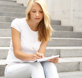 Attractive young girl sitting and writing in a notebook poster
