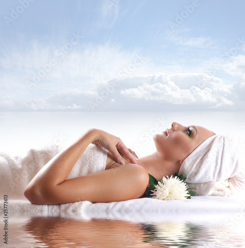 A young woman is relaxing while lying on a white towel