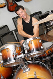 young man playing on drums in music store