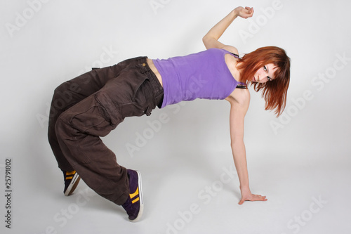 young redhead girl in hip-hop clothes in dance position, standin