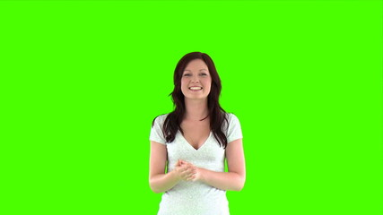 cheerful woman doing a thumbs up against a green screen