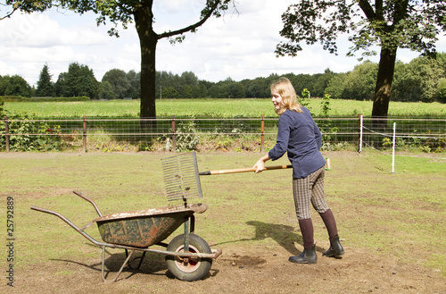 Girl cleaning the manure