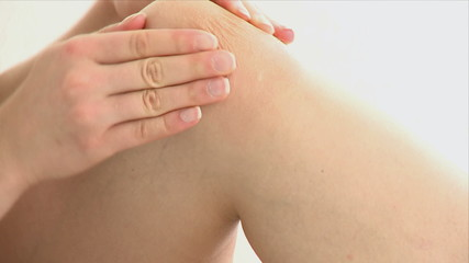 Attractive woman massaging her knee