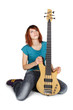 young beauty redhead girl sitting and holding bass guitar, looki