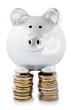 Cochon tirelire debout sur piles de monnaie