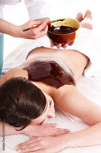 Girl having chocolate body mask .