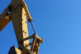 Hydraulic excavator arm against a blue sky poster