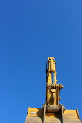 Hydraulic excavator arm against a blue sky