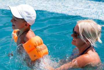 Smiling beautiful woman and little boy bathes in pool