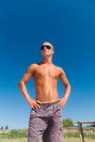 Image of a young masculine man posing at the beach poster