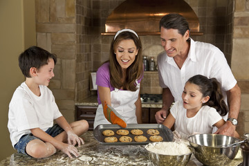 Attractive Family Baking and Eating Cookies In A Kitchen