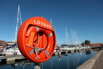 Large orange lifebuoy in Weymouth harbour with yachts behind