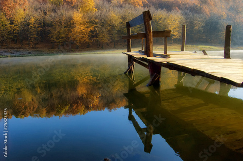 autumn morning at lake near a colorful orange forest