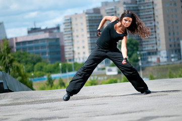 Beautiful girl dancing hip-hop over urban landscape