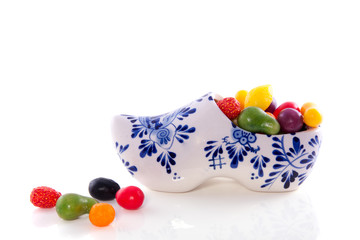 Old Dutch candy fruit in a Delft blue clog isolated over white