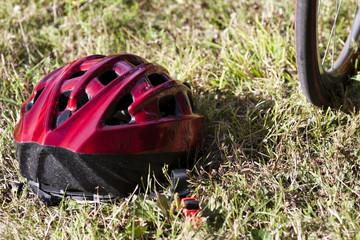 casque rouge posé sur l'herbe près d'une roue