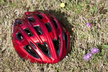 casque rouge posé sur l'herbe, près de fleurs