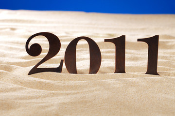 2011 new year metal numbers on beach sand
