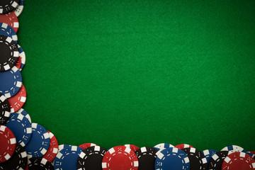 Gambling chips on green felt background
