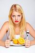 frustrierte frau isst eine orange mit besteck