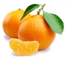Ripe tangerines with leaves and slices on white background
