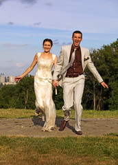Just marries happy couple running in the park