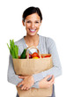 Pretty woman holding a grocery bag and smiling on white
