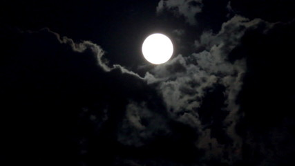 timelapse with moon moving between clouds