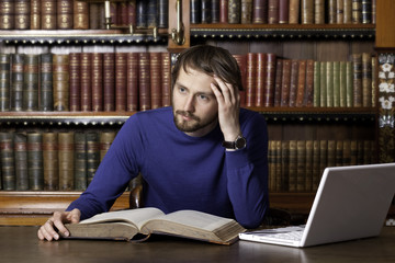 A young man over a book with laptop in classic library