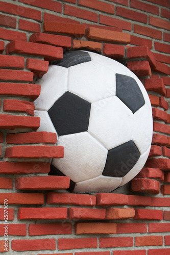 A soccer ball wedged into a brick wall