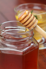 Jar and honey dipper with honey and a cup of tea with lemon
