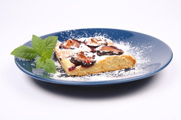 Piece of Plum Pie covered with powder sugar with a mint twig