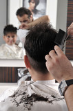 Professional hairdresser cutting child's hair in beauty saloon. poster