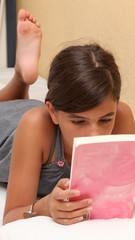 adolescante legge un libro sdraiata sul letto