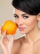 Portrait of beautiful woman, she holding fresh orange