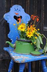 Stuhl mit Teekanne und Blumen