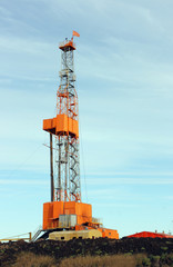 Orange oil derrick against blue sky