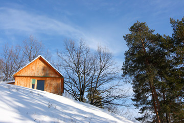 Wooden cottage against a blue sky in the winter